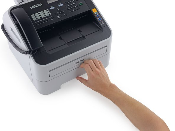 Grasp the paper tray at the front of the fax machine, and pull it straight out.