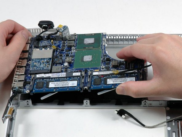 Lift the logic board up from the right side, and slide it up and out of the computer. Be careful that the right speaker, MagSafe board, and battery connector don't catch on the lower case.