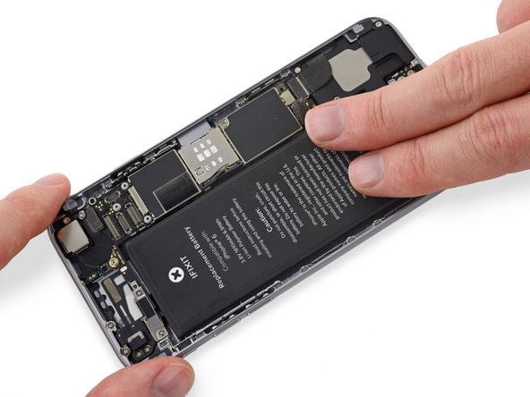 When the battery is correctly positioned, lay it down in the iPhone and press it firmly into place, allowing the adhesive strips to stick to the rear case.