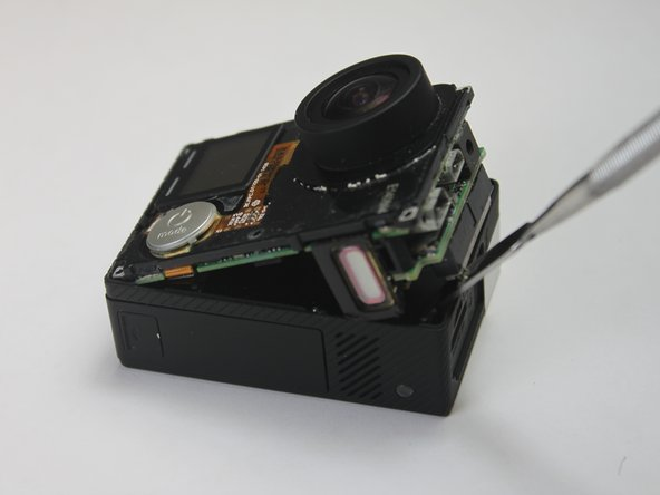 To remove the motherboard assembly from the camera casing, use the plastic opening tool on the lens side of the camera to pry the motherboard assembly out of the camera housing.