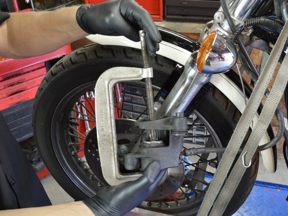 Position the screw of a large C clamp so that the head of the screw is pressing against the inside of the brake piston.