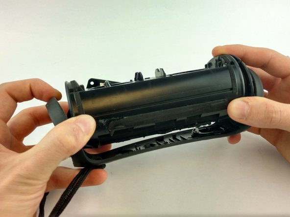 Carefully remove outer frame to expose the inner components of the speaker.