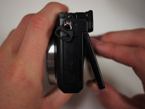 Lift the LCD screen with your fingers such that the screen is bent slightly away from the camera.