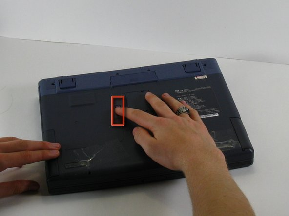With one hand slide and hold the tab shown.