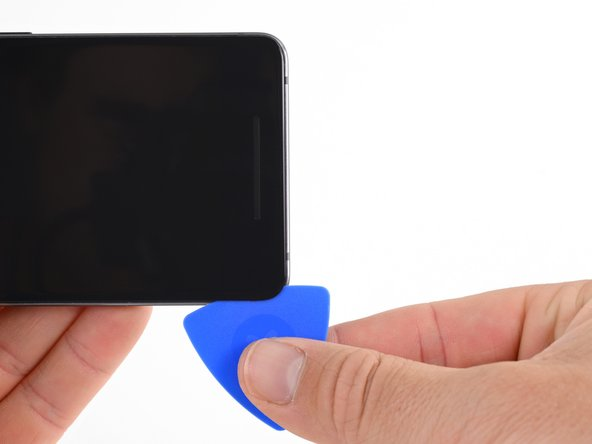 Slide the pick around the bottom-left corner and along the bottom of the phone. Keep pick at a slight angle away from the screen to avoid damage to the OLED corners.