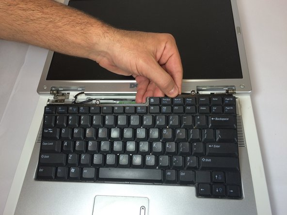 Gently lift the keyboard away from the laptop without harming the cord that is located at the bottom of the keyboard.