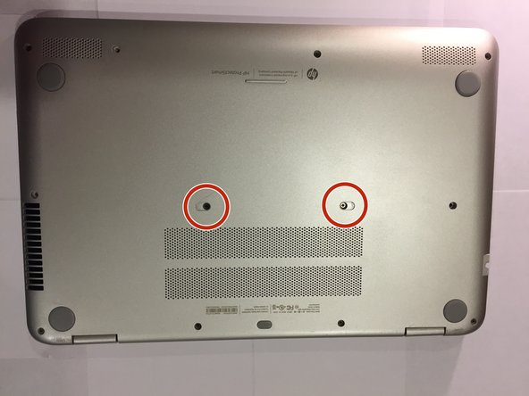 Flip the laptop over on its back and remove the two depressed stickers in the middle to reveal the two central 6.0 mm Phillips-head  screws.