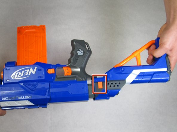 Remove the stock of the blaster by pushing the orange tabs downward while pulling the stock away from the blaster.
