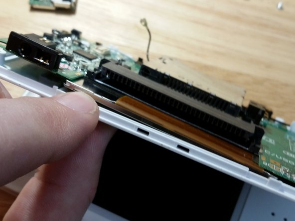 Flip the motherboard around as shown. Be gentle as the flex cable is fragile.