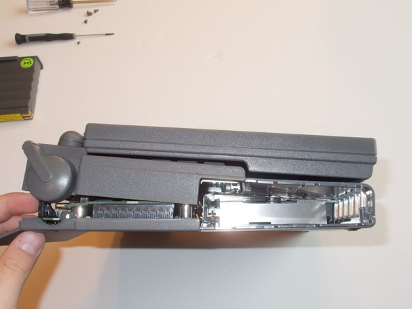 CAREFULLY lift the back of the screen and keyboard unit(the top of the computer) and GENTLY push the front left and right corners away from the bottom unit until a click is heard. Then, SLOWLY lift the top unit and remove the interconnect cable (the large somewhat brittle cable connecting the two halves) from its socket in the sisterboard.