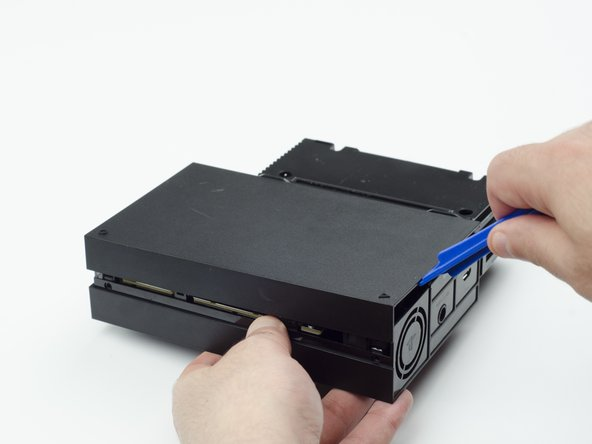 With the plastic opening tool, carefully pry the console shell panel free and lift it away.
