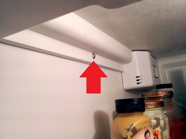 Remove the wire cover in the top left edge of the fridge. It's held in place by one Phillips head screw.