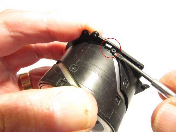 To remove the lens core from the innermost black barrel, push one of three pegs towards a slot in the flange. With light pressure on the front of the lens (but not on the protective lens shutter), all three pegs will pop through their slots, allowing the lens core to be removed.