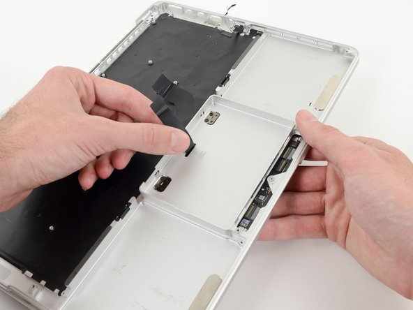 Once the trackpad is free of the upper case, guide the trackpad ribbon cable through the slot cut in the upper case.