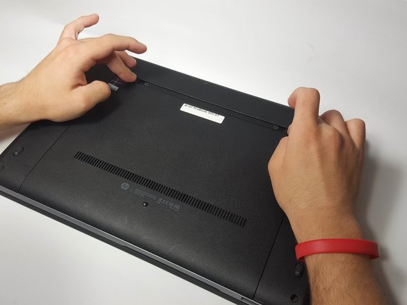 Slide the two battery release latches towards the center of the laptop to release the battery.