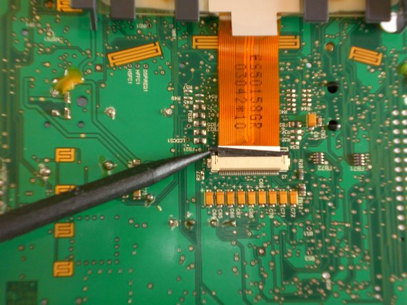 Push the black clip holding the ribbon cable out of its casing using the plastic opening tool.