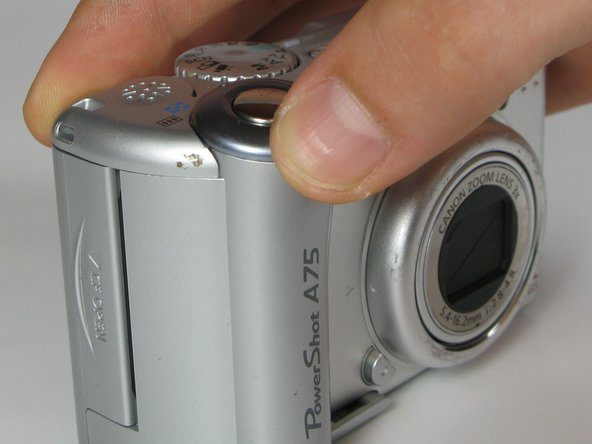 Lift the shutter button and speaker part from the top of the camera.
