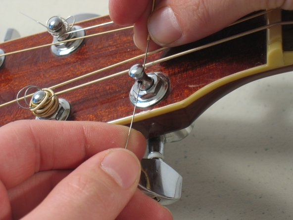 Insert the other side of the guitar string through the keyhole of the guitar peg.