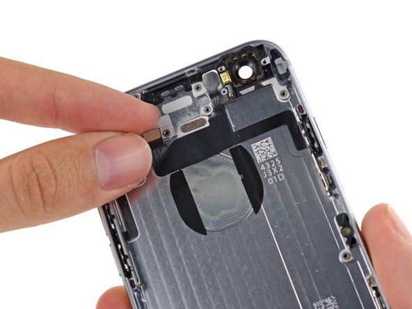 Begin to peel the flash/microphone/power button assembly cable up from the rear case starting from the connector end.