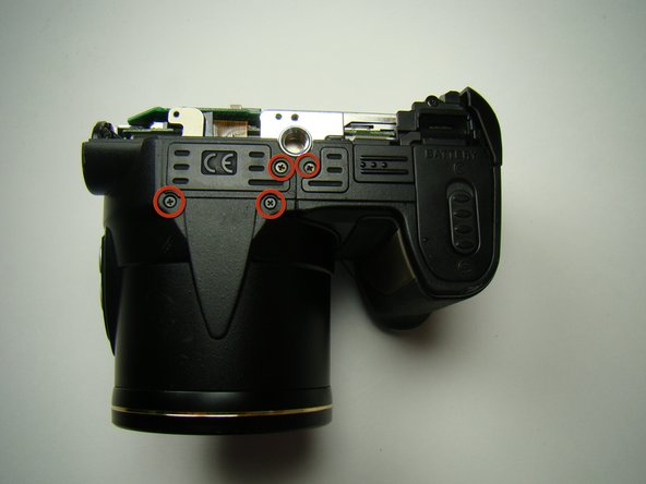 Remove all four of the screws on the bottom of the camera.
