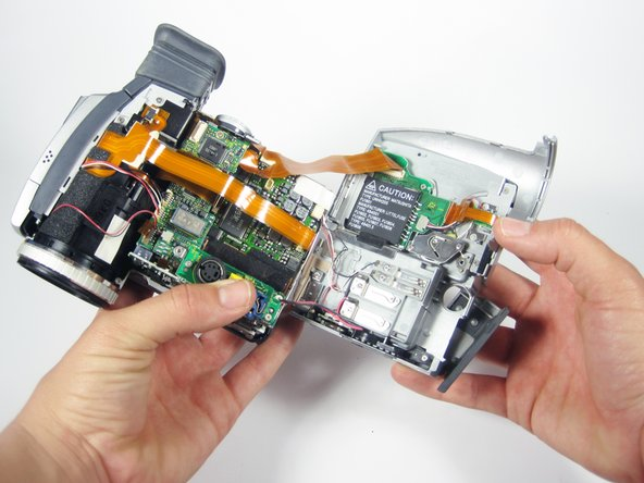 The side of the device should now be open as shown.  Again, there are wire connections between the side cover and the body of the camcorder. Do not separate the two entirely!