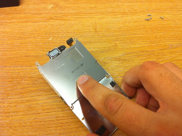 To remove the screen from the metal backing plate, apply some pressure to the back of the screen plate that you can see through the metal backing plate.