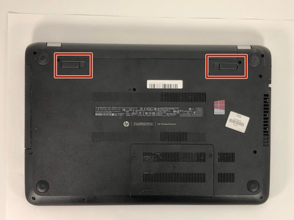Slide the battery locks towards the center of the laptop. The battery will detach automatically.