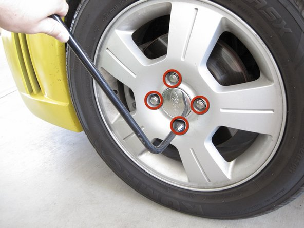 Use a 19 mm lug wrench to loosen each lug nut a half turn.
