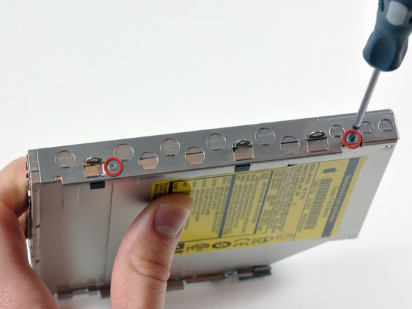 Remove the two small silver Phillips screws attaching the bracket to the left side of the optical drive.
