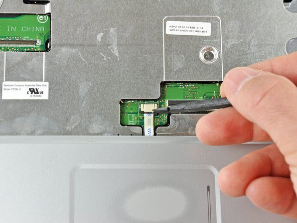 Use a spudger to pull the touch pad connector latch towards the ribbon cable.