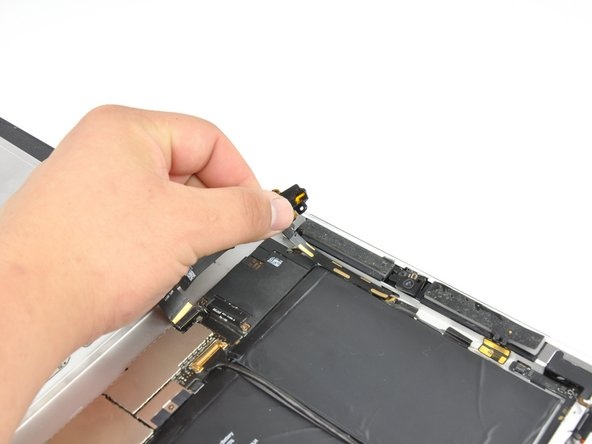Carefully peel the front camera and microphone cables off the rear panel.