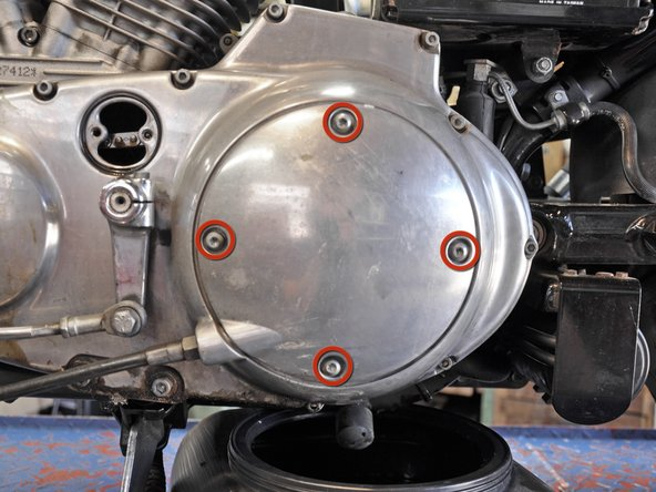 Using a T27 screwdriver bit, remove the four screws holding the clutch inspection cover in place.