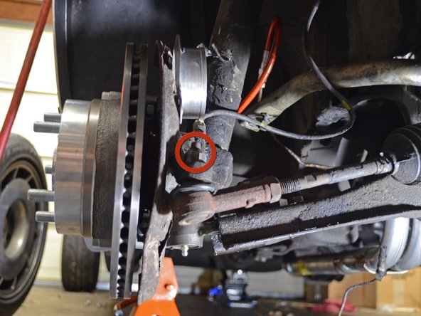 Use an impact wrench to remove the 19 mm tie rod end nut near the brake rotor.