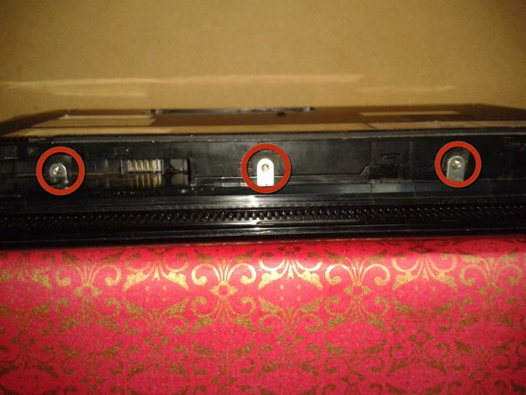 Remove the three screws in the silver tabs at the back of the keyboard. The red circles show where they are located at the back of the base under the screen.