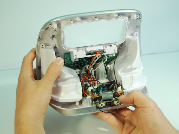 Be careful when removing the bottom panel. The plastic tab that runs alongside the right speaker between the upper brown radio motherboard and the lower green audio daughterboard may damage the device if the bottom panel is improperly removed.
