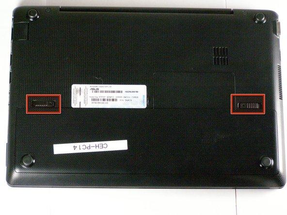Utilisez les deux index pour pousser les deux languettes à ressort vers le centre de l'ordinateur portable.
