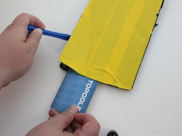Insert the plastic opening tool on one of the corners of the device.