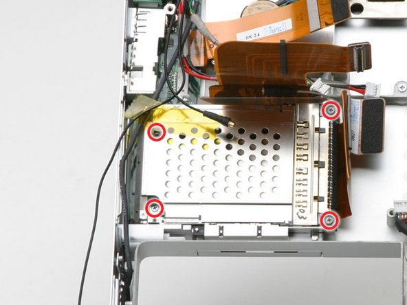 Remove the Phillips screw from each corner of the PC card cage (4 screws total).