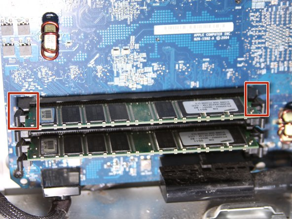 Use your thumbs to push the RAM ejector pins to the sides.