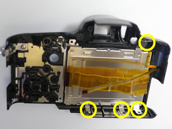 Release the hold clips that hold the LCD retainer in place.