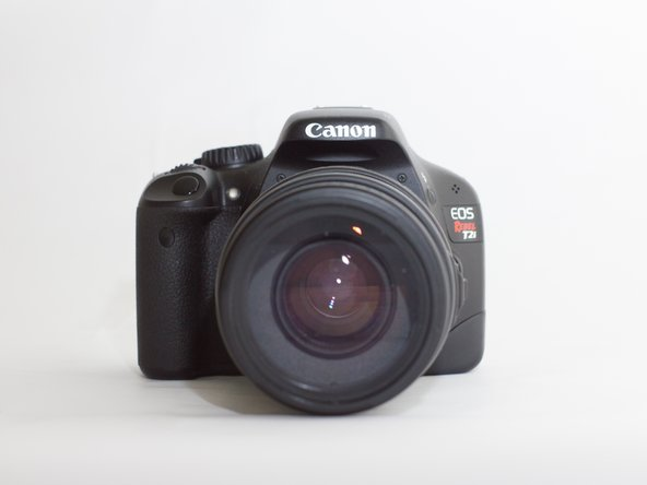 While holding both the camera's body and lens securely, press and hold the lens release button located below the marking plate.
