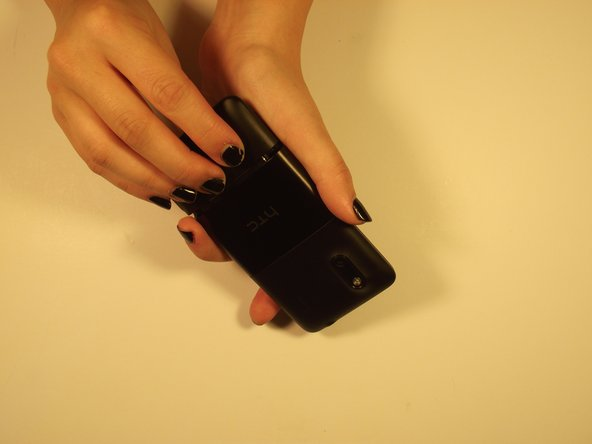 Use fingers on either end of the button edges of the phone to pull back cover off. It should slide off.