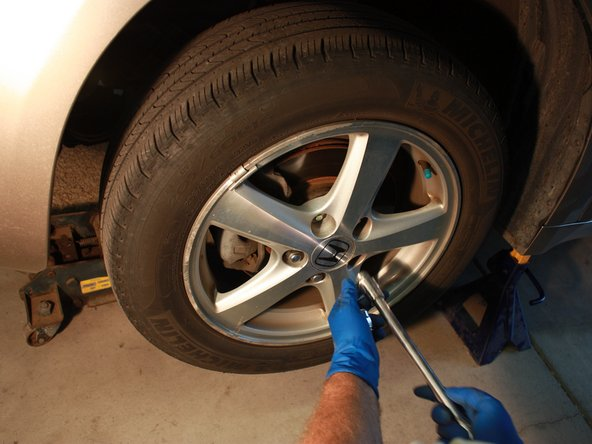 Once the car is raised, remove the lug nuts with the ratchet attached to a 3/4'' socket.