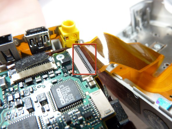 Unclip the clip holding the ribbon cable in.