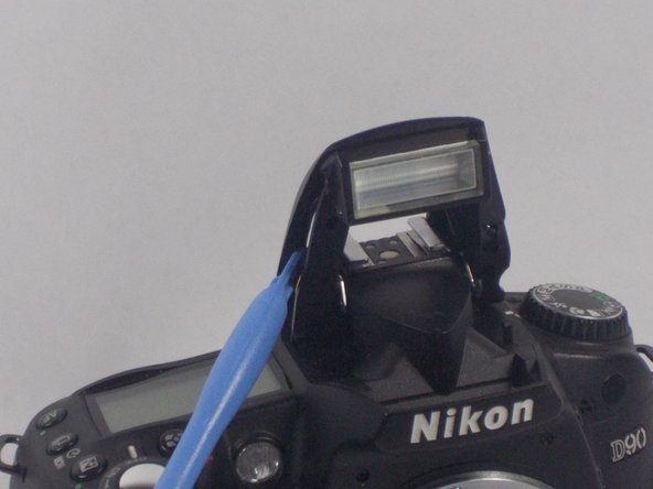Use a plastic opening tool and carefully pry open the top casing of the flash.