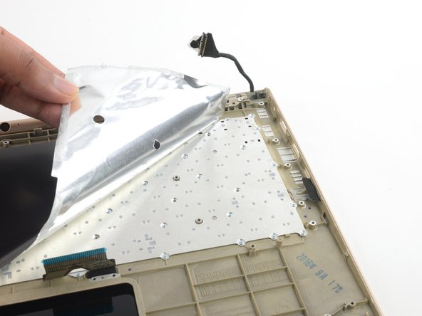 Keyboard is hidden beneath thin-film insulator taped in place. If you're performing a keyboard replacement, you'll need to buy replacement adhesive for this film.
