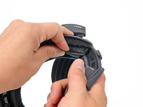 Peel back the rubber battery cover from the inner left side of the frame.