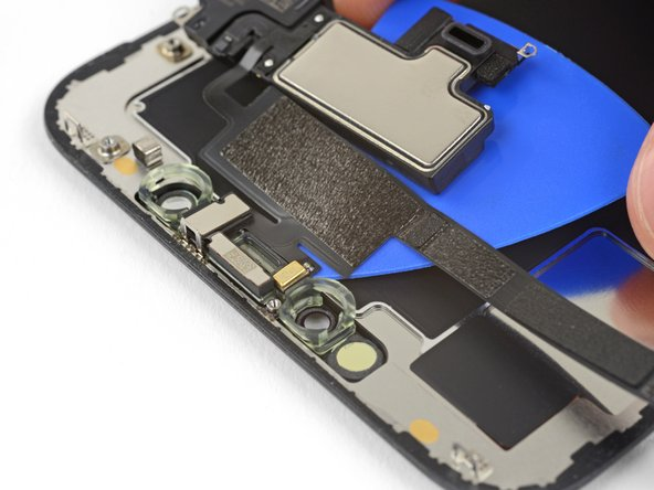 Carefully slide the edge of your opening pick underneath the flex cable below the microphone.