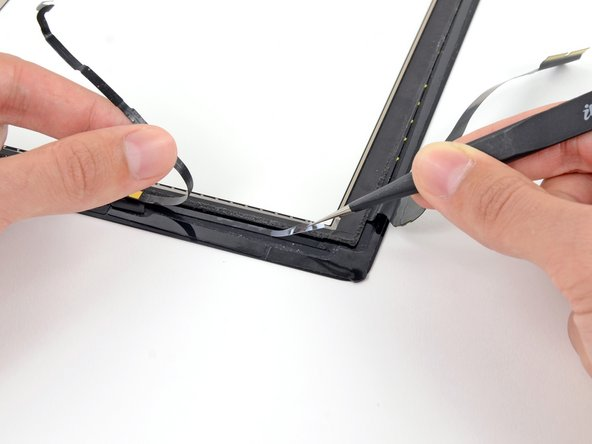 Use a pair of tweezers to peel the clear backing up off the adhesive strip directly underneath the home button ribbon cable.