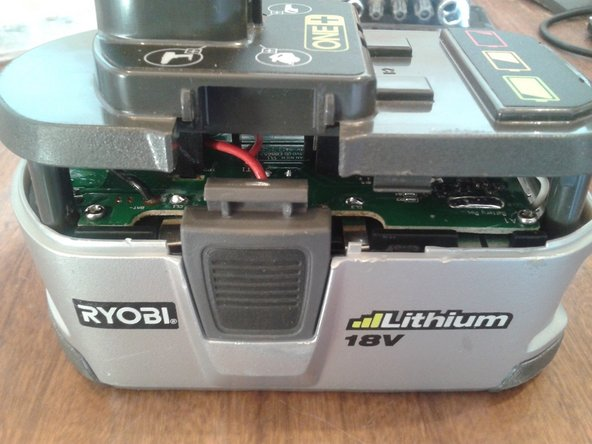 Once there is enough gap, reach in and hold the battery terminal assembly, while sliding off the top cover.